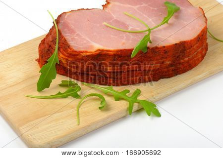 stack of sliced smoked pork meat with arugula leaves on wooden cutting board - close up
