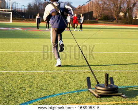 Track and field sprinter pulling a weighted sled on a green turf field during sprinting practice
