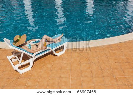 Young woman in hat relaxing on sun lounger in the edge of swimming pool