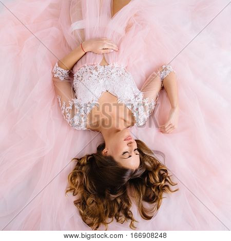 beautiful young woman in a pink dressing gown lying on the bed top view