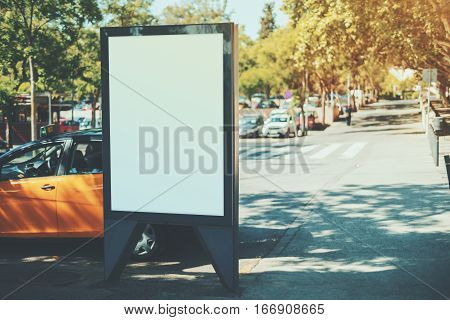 White billboard with copy space for your text message or content public information board in european city advertising mock up empty banner near yellow taxi and crosswalk at beautiful sunny day
