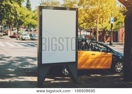 White billboard with copy space for your text message or content public information board in european city advertising mock up empty banner near yellow taxi and crosswalk at sunny day