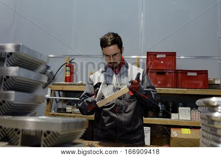 ST. PETERSBURG, RUSSIA - NOVEMBER 30, 2016: Man at work in the department of mechanical processing of Vitrulux. It is one of leading companies in development and manufacturing of lighting solutions