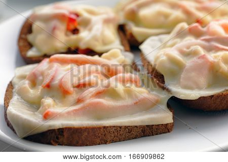 Sandwiches with chicken meat, red bell pepper, and cheese on a plate