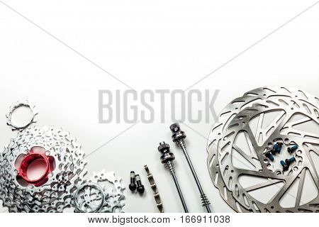 Mountain bike spares  cassette bolts chain skewers and brake disk rotors on white background