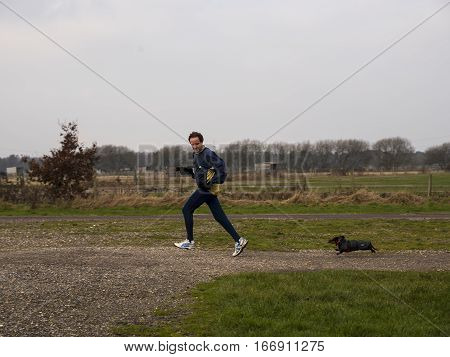 Man in winter running gear running off road looking over his shoulder where he is followed by miniature dachshund