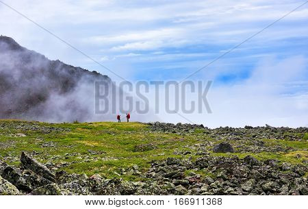 Edge world. Two men standing on edge of hanging valley in mountain tundra on background of rising mist. Eastern Siberia. Russia