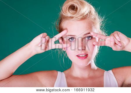 Gestures mystery concept. Young woman having pin up hair with fingers close to her eyes looking mysterious and enigmatic.