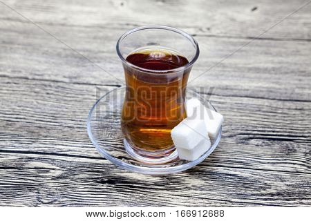 Turkish tea. A small glass of Turkish tea, a plate of sugar on a wooden table. Can be used as photos for the menu of the Eastern Turkish confectionery.
