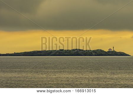 Island lighthouse with orange sky and grey clouds Vancouver Island Canada