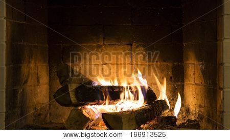 Real Wood Fire Burning in a Clean Brick Fireplace.