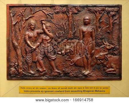 KOLKATA,INDIA - FEBRUARY 09, 2016: Indra prevents an ignorant cowherd from assaulting Bhagavan Mahavira, Street bas relief on the wall of Jain Temple (also called Parshwanath Temple) in Kolkata, India
