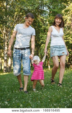 Young beautiful couple walking on the grass in park with their one year old daughter and having fun