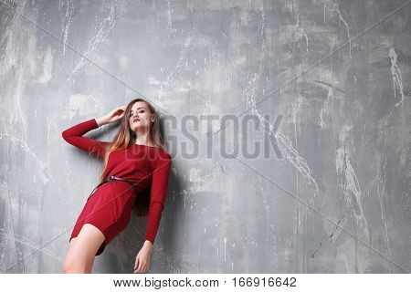 Attractive woman in red gown with beautiful makeup posing on grey background