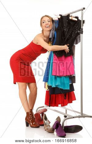 Young woman stands near her clothes rack with lots of dressesand embraces clothes.isolated on white