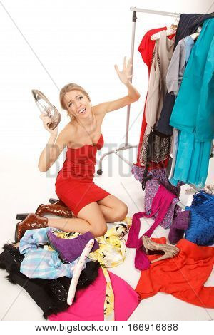 Young woman sits near her clothes rack with lots of dressesand some clothes is on the floorand she is holding her shoe and scream!