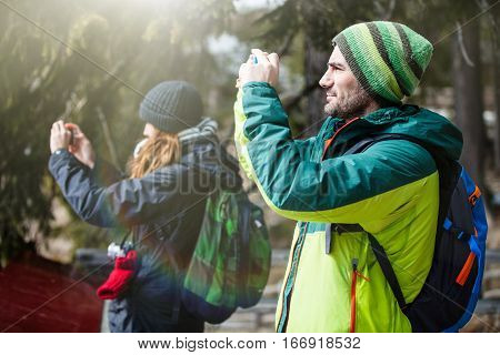 Hiking and photography. Two people taking a picture. Two young people, a men and a woman, with clothing hiking with backpack, taking a picture with a cell phone. Excursions and leisure concept.