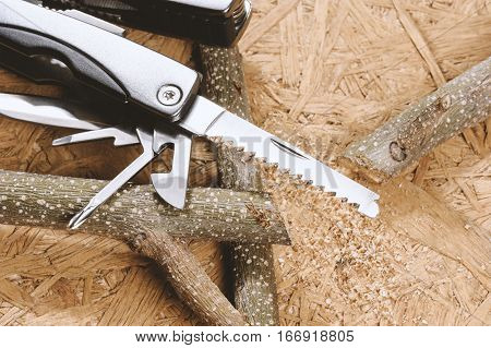 using handsaw cutting the branch, multifunction tool