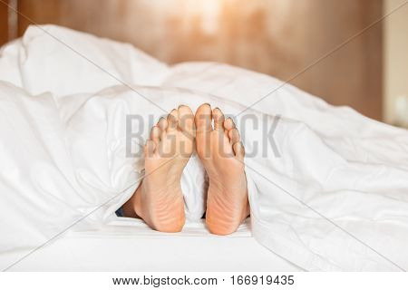 Woman feet under white blanket side view. Beautiful young woman feet with blue pedicure on the bed. Sleeping woman legs under the white blanket