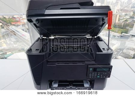 office printer is repaired with red screwdriver