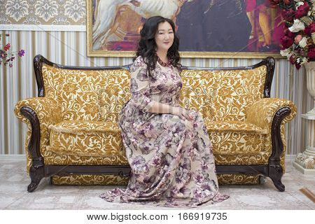 A Full Asian Woman Sitting On The Sofa In The Living Room.