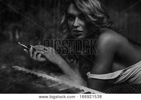 Young woman musician sensual fashion portrait. Smoking and playing piano. Black and white film style colors.