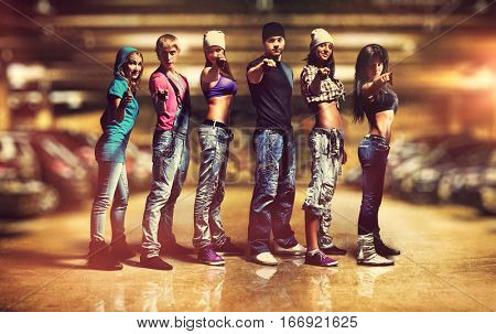 Six people modern dancers team. Showing pointing hand sign. Underground car parking interior.