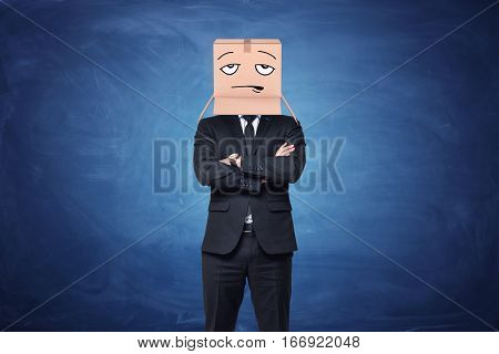 Businessman is wearing a cardboard box on his head with painted disappointed face on blue chalkboard background. Hidden emotions. Working routine.