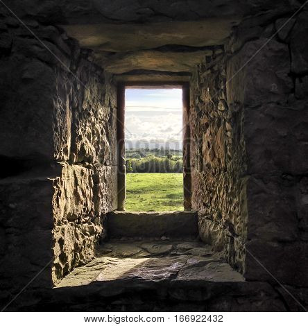 View through a stone castle window to green fields in Ireland