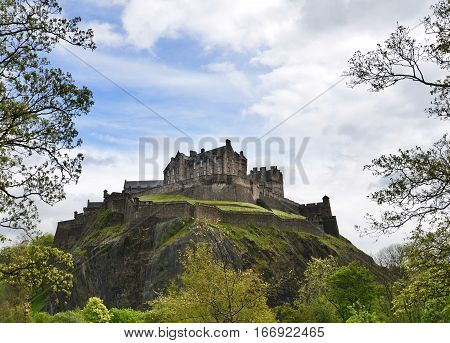 Edinburgh Castle sitting above the city on a large rock and framed by trees. The rock is a plug to an extinct volcano.