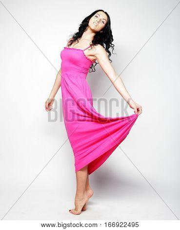 Full length of brunette female in pink dress posing