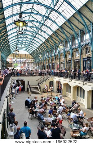 LONDON UK - MAY 19 2014: An audience watches a musical performance in Covent Garden Market