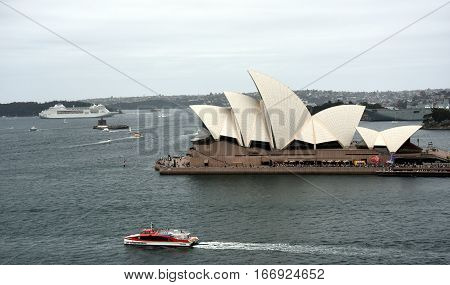 Sydney Australia - January 26 2017. Ferry in front of the Opera House big cruise ship in the background. Big crowd at Opera House celebrating Australia Day.