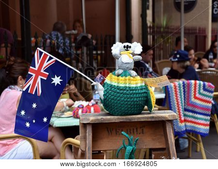 Sydney Australia - January 26 2017. Knitten Koala sitting on a yellow and green knitten teapot cosy which was inspired by Australia day. Australia flag next to the installation at The Tea Cosy cafe.