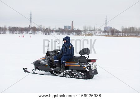KAZAN, RUSSIA - JANUARY 19, 2017: Russian MoE lifeguard with snowmobile - rescuer on ice at winter day during Christ's baptism holiday , telephoto