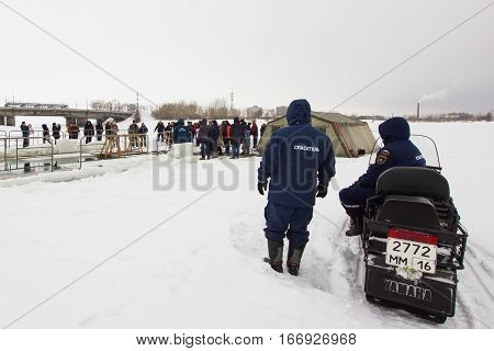 KAZAN, RUSSIA - JANUARY 19, 2017: tree russian MoE lifeguards with snowmobile - rescuer on ice at winter day during Christ's baptism holiday, telephoto