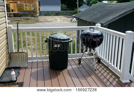 HARBOR SPRINGS, MICHIGAN / UNITED STATES - AUGUST 4, 2016: A snow shovel, an Ace garbage can, and a Weber grill stand on the back deck of a home in Harbor Springs.