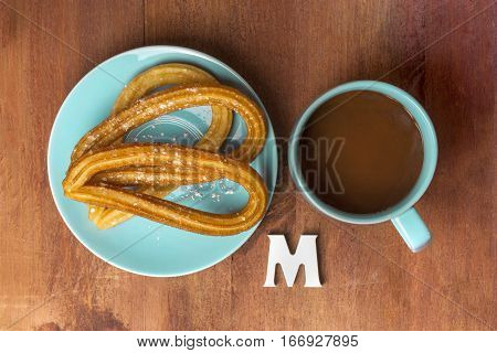 A plate of churros, traditional Spanish, especially Madrid, dessert, particularly for Sunday breakfast, with a cup of hot chocolate, shot from above with the letter M