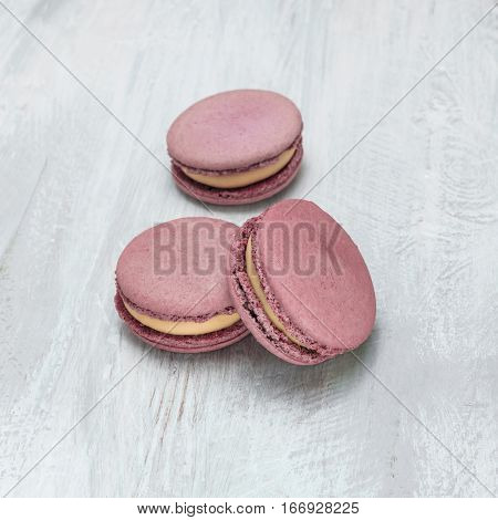 A square photo of pink macarons on a pale whitewashed board, with copy space. Selective focus