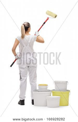 Full length rear shot of a female painter painting with a paint roller isolated on white background