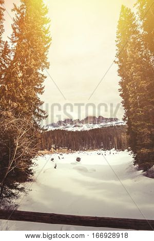 Frozen lake, fir forest and mountains. Lake Carezza in South Tyrol in Italy. Beautiful landscape in northern Italy, frozen lake with snow.