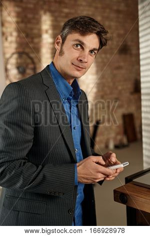 Handsome businessman holding mobilephone, looking at camera.