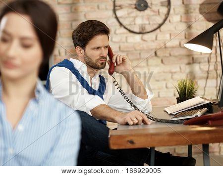 Businessman talking on landline phone, sitting at desk.