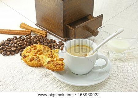 Coffee cup, biscuit grinder and coffeebeans on table. poster