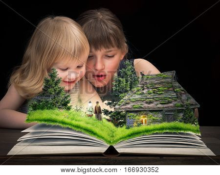 The children delighted in watching a fairy tale on the pages of an open book. Tale characters - the old man and old woman. Rustic old house a forest glade with flowers.