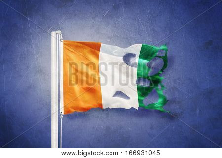 Torn flag of Cote d'Ivoire flying against grunge background