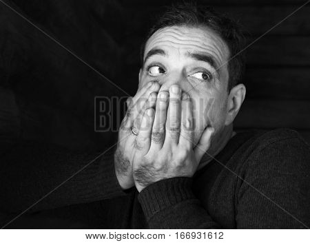 Adult sad man. He closed his mouth with his hands, looking up. Black and white portrait