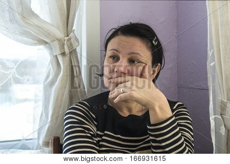 Portrait of sad mature woman sitting in her room by the window