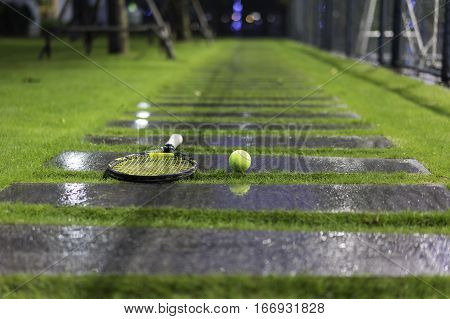 Tennis Ball And Racket On Wet Walkway And Grass After Raining
