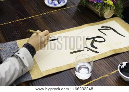 Calligrapher Painting Words On Paper. Calligraphy Is A Traditional Culture In Eastern Lunar New Year